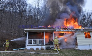Firefighters battle a fire at the home of Donald Cassidy on Ky. Rt. 344. - Photo by Dennis Brown