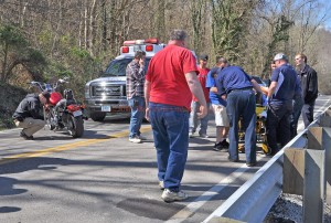 Rescue personnel prepare to transfer a motorcycle operator into an ambulance following an accident near Vanceburg Wednesday afternoon as Deputy Eric Poynter examines the motorcycle. - Photo by Dennis Brown