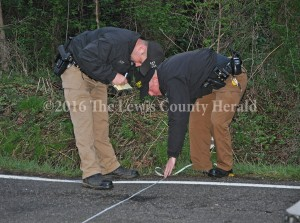 Deputy Matt Ross and Deputy Mark Sparks take measurements at the scene of an accident Thursday evening at Dugan's Curve, east of Vanceburg on Ky. Rt. 8. - Photo by Dennis Brown