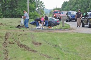 Officials help to clean up at the scene of a single vehicle accident on Memorial Day. Only minor injuries were reported. - Photo by Dennis Brown