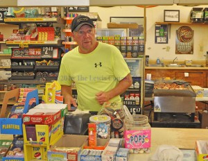 Steve Applegate waits on a customer at Steve's Market. The neighborhood grocery will close on Saturday. - Photo by Dennis Brown