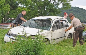 Deputy Matt Ross, left, and Sheriff Johnny Bivens examine the scene of a single vehicle accident Wednesday afternoon on Ribolt-Epworth Road. A Tollesboro woman was airlifted to a Huntington, West Virginia, trauma center following the crash. - Photo by Dennis Brown