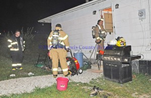 Firefighters work to remove smoke from a Quicks Run residence after a small fire. - Photo by Dennis Brown