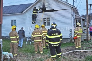 Firefighters work to contain a fire at a Vanceburg home on Monday. - Dennis Brown Photo