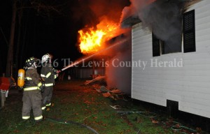Firefighters work to contain a fire at the home of Rocky Jamison on Montgomery Road. - Dennis Brown Photo