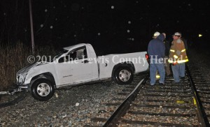 Emergency responders examine the scene of a fatal accident Sunday night at Quincy. The driver of the pick-up was ejected from the vehicle and perished at the scene. - Dennis Brown Photo