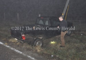 Deputy Eric Poynter looks over the scene of a single vehicle accident early Sunday in which the vehicle's operator left before first responders arrived. - Dennis Brown Photo