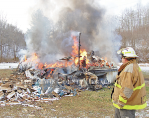 Garrison firefighter Hammer Cooper looks over the scene of a mobile home fire Monday morning on Mills Branch Road. No injuries were reported. The mobile home and all its contents were destroyed in the fire. - Dennis Brown Photo
