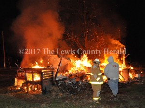 Firefighters Hammer Cooper and Curtis Brewer at the scene of a mobile home fire in Garrison early Friday. The cause of the fire is under investigation. - Dennis Brown Photo
