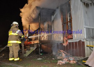 A Garrison firefighter works to bring a mobile home fire under control Saturday night. No injuries were reported as a result of the incident. The cause is under investigation. - Dennis Brown Photo
