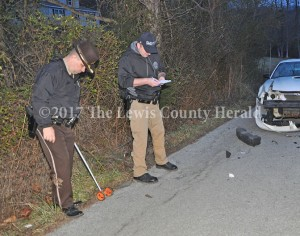 Sheriff Johnny Bivens and Deputy Matt Ross collect information at the scene of a fatal accident on Rock Creek Road at Quincy Monday evening. - Dennis Brown Photo