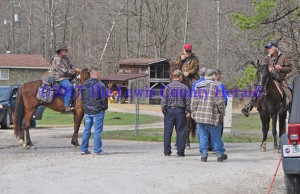 Sheriff Johnny Bivens, standing at left, talks with volunteers on horseback near the location where Justin Johnson's abandoned truck was found. - Dennis Brown Photo