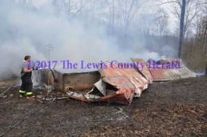 A firefighter sprays water on a fire that destroyed a cabin off Little Trace Road near Garrison. - Dennis Brown Photo