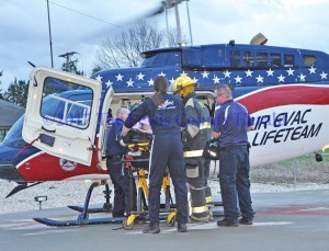 First responders transfer a patient to a medical helicopter following a single-vehicle accident on the AA Highway near Ribolt. - Dennis Brown Photo