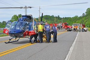 Emergency workers load a patient onto a medical helicopter following an accident Monday afternoon at Garrison. - Dennis Brown Photo