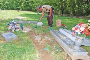 Deputy Bryon Walker collects evidence in Waring Cemetery at Garrison. Extensive damage was discovered Friday morning to indicate the vehicle involved is a 1997-2001 Honda CRV. - Dennis Brown Photo