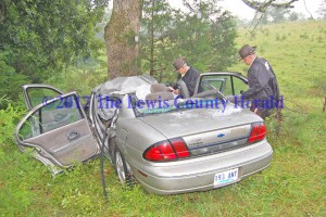 Deputy Gary Sparks and Deputy Matt Ross collect information at the scene of a single-vehicle accident on the AA Highway near Tollesboro. - Dennis Brown Photo