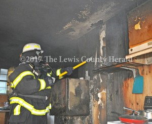 Black Oak Fire Chief Curtis Brewer checks inside a kitchen wall for signs of fire at a home on Rock Run. The home sustained extensive smoke and water damage as a result of the fire. - Dennis Brown Photo