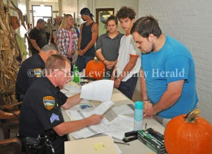 Suspects wait in line to be processed Friday during Operation Fall Harvest. The drug roundup began before daylight. - Dennis Brown Photo