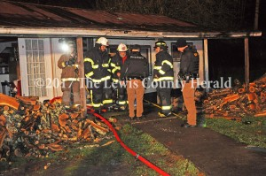 Firefighters and deputies examine the scene of a residential fire on Little Trace Branch Road late Wednesday. No one was hurt as a result of the fire. - Dennis Brown Fire