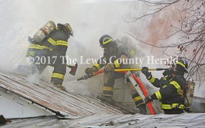 Firefighters work to bring a fire under control on Happy Hollow Road Wednesday morning. No one was hurt although the home sustained extensive damage. - Dennis Brown Photo