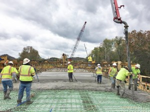 Workers work to place a concrete deck on the new Garrison bridge. - Brandon Howe Photo